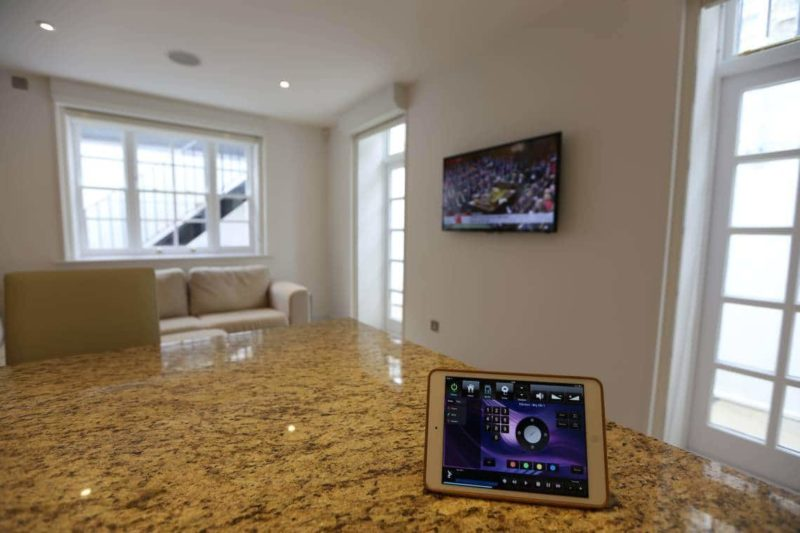 Crestron Installation SW1 Kitchen showing iPad and TV 800x533 - Case Study: Whole Home Audio Video - Crestron Installation Pimlico, London